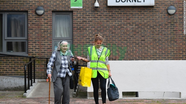 A council worker helps a resident leave Dorney Tower residential block on the Chalcots Estate in north Lo<em></em>ndon on June 25, 2017.